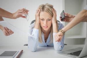Foto Frau stützt genervt Kopf in Hände